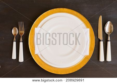 Tableware - set of white and golden plates and utencils on dark wooden table