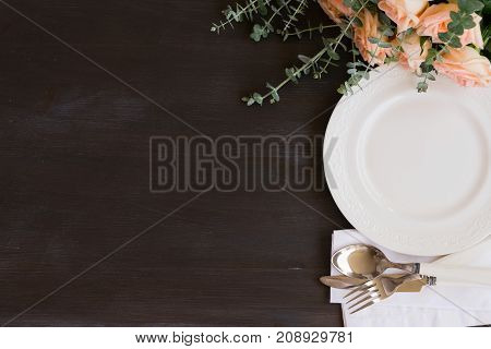 Tableware - set of plates and utencils on dark wooden background with copy space