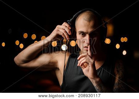 Handsome tattooed nightclub DJ in headphones feels the music on the background of night club lights