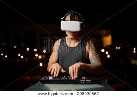 Muscular and tattooed nightclub DJ in night vision glasses with headphones plays the music on the background of lights
