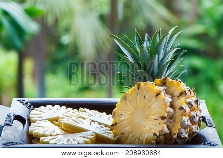 Pineapple in natural conditions on a beautiful tropical background. Exotic fruits