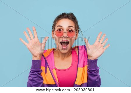 Portrait of pretty hipster girl in colorful clothing and sunglasses looking excited on blue background.