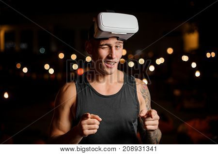 Handsome muscular and tattooed man dressed in black shirt in night vision glasses winks on the background of lights