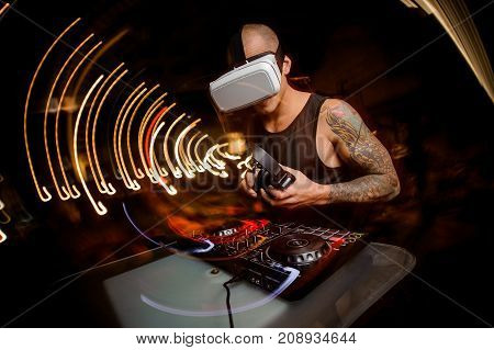 DJ man in virtual reality glasses on the background of a party. The concept of future technologies.