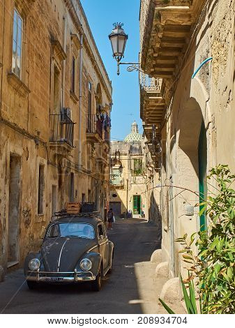 Lecce Italy - August 17 2017. Classic Volkswagen beetle crossing a typical street of southern Italy.