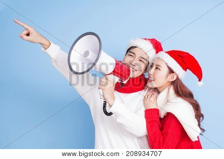 couple take microphone and show something with merry christmas on the blue background