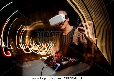 Sporty young guy DJ in glasses of virtual reality against the background of a night city. The concept of the future