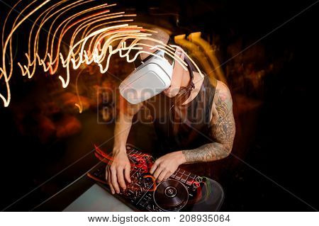 DJ man in virtual reality glasses on the background of a party.
