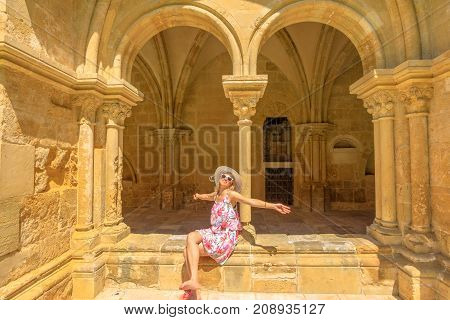 Female tourist enjoying in university town of Coimbra. Freedom woman with open arms at old Coimbra Cathedral or Se Vhelha de Coimbra in a sunny day. Gothic romanesque colonnade on background.
