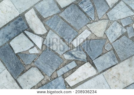 Marble tiles of different shapes laid out on a flat surface. The tiles are rectangular and triangular in shape. Have gray beige and blue. The seams between the tiles filled with concrete or cement.