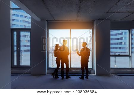 Real estate concept with agent and couple near big panoramic window