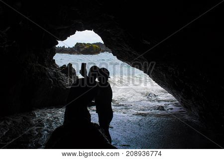 Silhouetted Couple Takes Selfie in Sea Cave with Ocean Beyond