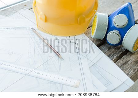 Engineering workplace drawings protective construction helmet and dust mask on the desktop the view from the top