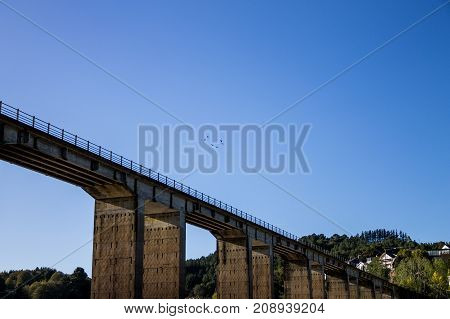 Ducks flying over a bridge in clear sky