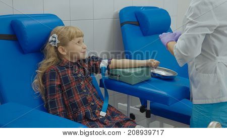 Little girl having a blood test, nurse is preparing a child for taking blood sample in medical surgery from a vein in the arm.