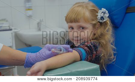 Portrait of little girl at blood test. Nurse is taking blood sample in medical surgery from a vein in the arm. Child looking at camera and smiling.