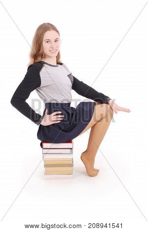 Education people teenager and school concept - teenager school girl sitting on stack of books. Isolated over white