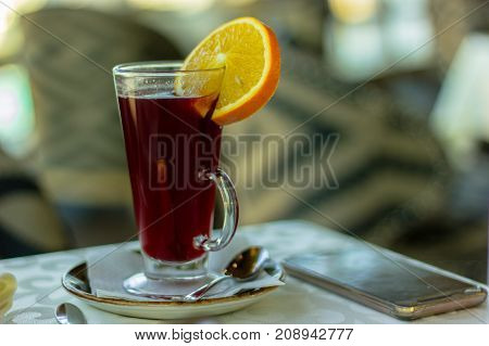 hot tea with an orange and with phone on the table