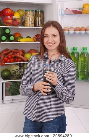 Young girl holding cola on the refrigerator background