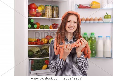 Young girl holds sausages on the refrigerator background. Beautiful young girl near the fridge.