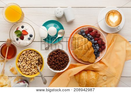 Rich breakfast menu background. French crusty croissants, muesli, glass of orange fresh, yogurt, coffee, berries, honey and boiled eggs for tasty morning meals on wooden table, top view