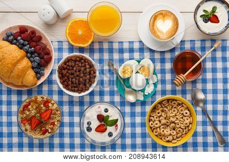 Rich breakfast menu background. French crusty croissants, muesli, glass of orange fresh, yogurt, coffee, berries, honey and boiled eggs for tasty morning meals on checkered tablecloth, top view