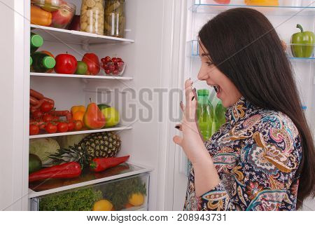 Young girl with an amused face on the refrigerator background. Beautiful young girl near the fridge.