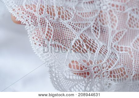 Beautiful delicate openwork white lace in hand
