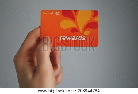 Sydney Australia - October 15 2017: Female caucasian hand is holding a Woolworths Rewards loyalty card this loyalty program gives money off shopping. Woolworths Supermarkets is an Australian market leader grocery store chain.