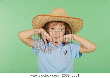 Young girl with light hair holding a straw hat in hand isolated on green background