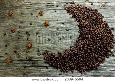 Fried black coffee beans located in the shape of the moon and anise like stars on a wooden background. Coffee beans in the shape of the moon. View from above