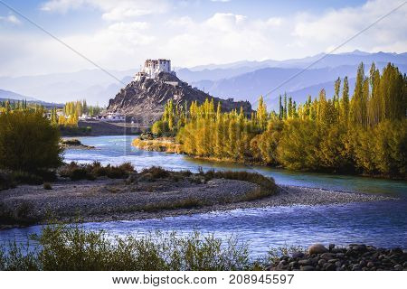 Stakna Gompa and Indus river before sunset with cloudy sky and mountains background