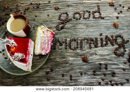 Good morning from coffee beans. A cup of coffee and a cake on a wooden background strewn anise. Greeting for breakfast. View from above