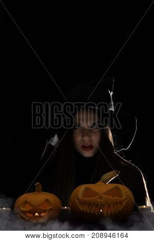 Halloween Witch With A Magic Pumpkin. Beautiful Young Woman In Witches Hat And Costume Holding Carve