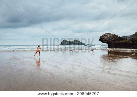 Boy runs on the ocean beach after rain