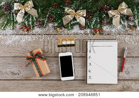 Christmas online shopping. Smartphone, credit card and presents list with copy space on wooden table with holiday garland border. Top view, preparing for winter holidays concept