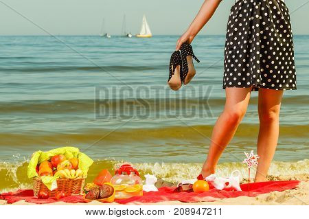 Summertime relaxation and recreation concept. Woman in retro dress having picnic near sea having basket with fruits and red blanket.