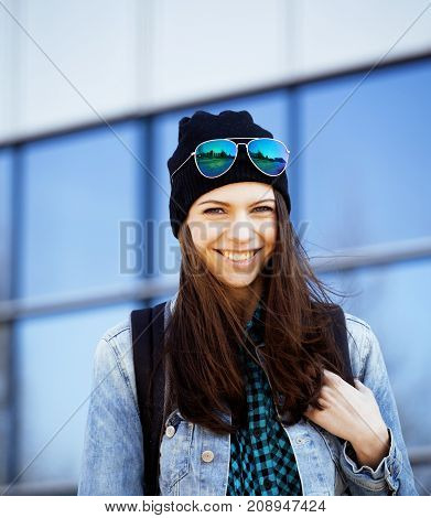 young pretty girl near business building walking, student teenager on blue
