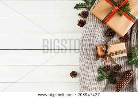 Prepare for new year, xmas. Presents on white wood table background. Handmade scarf, xmas boxes, fir branch, cones. Top view, copy space, flat lay. Winter holiday concept