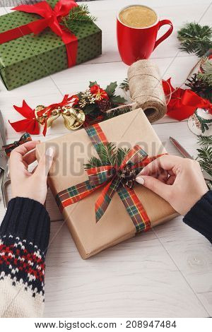 Creative diy hobby. Making bow on modern handmade xmas present, box in craft paper with red green checkered ribbon. Woman's hands on white wood table with fir tree branches, gift decoration.