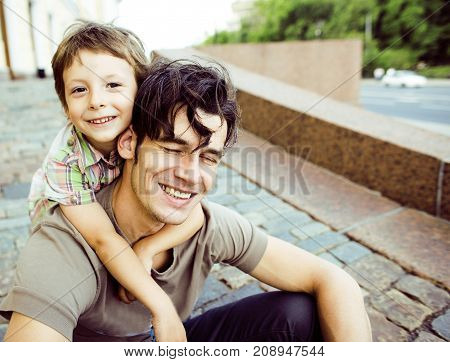 little son with father in city hagging and smiling, casual look close up