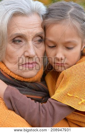 Close up portrait of sad grandmother with granddaughter