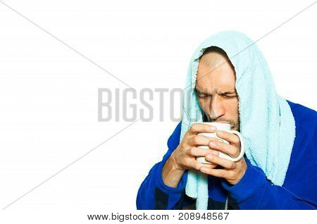 Young sick man have common cold flu and he is drinking a cup of hot tea while he is wearing towel on the head and thick winter clothes partially isolated on the white background