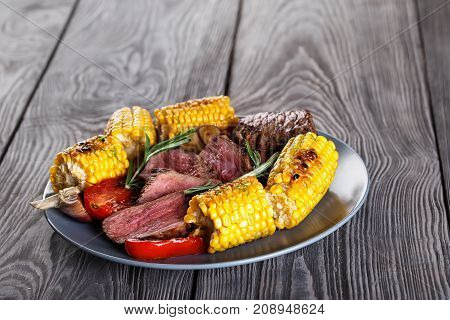 Blue clay plate with slices of mildly fried steak and corn. Wooden background. The concept of natural traditional food.