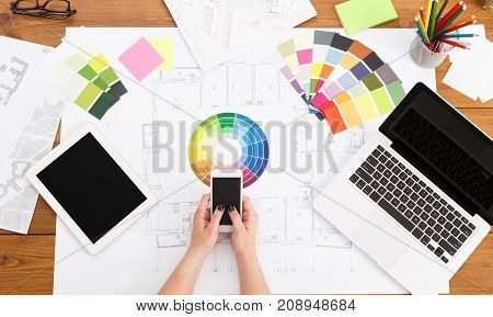 Architect drawing on architectural project. Top view on unrecognizable designer hands working with building blueprint, using smartphone with blank screen, mockup