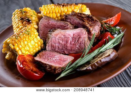 Clay plate with slices of chopped donated meat and corn on a wooden table. The concept of natural traditional food.