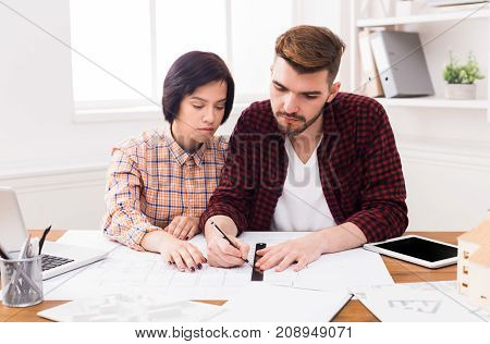 Two young designers sitting at table and working on project together, architects planning new building blueprint in office