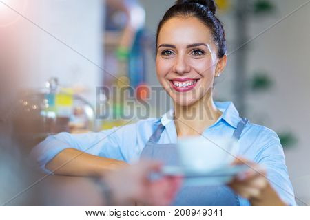 Coffee shop barista serving coffee