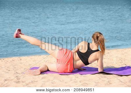 Sporty woman training on sea beach