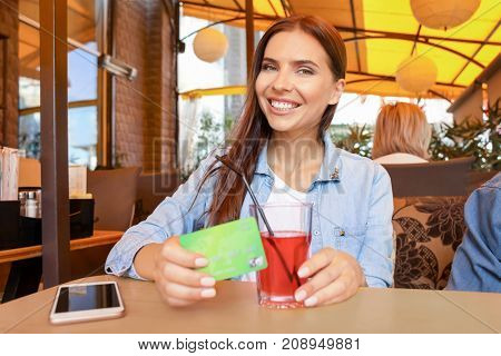 Young woman with credit card and smartphone in cafe